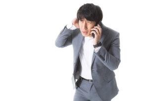 電話で謝罪する男性