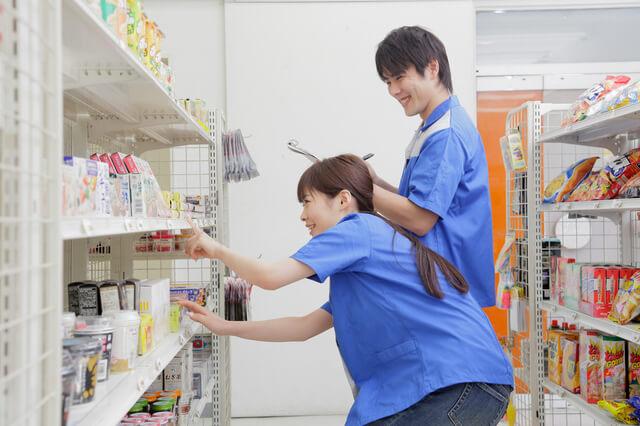商品を確認するコンビニ店員の男女